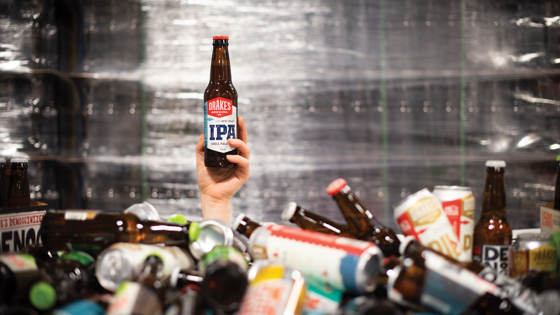 A bottle of Drake's Best Coast IPA being held above a pile of cans and bottles